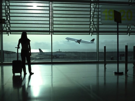 Woman with a suitcase waiting in the airport Stock Photo
