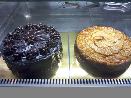 Chocolate cake and apple cake inside a showcase