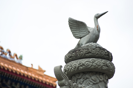 Close up Bird sculpture on top of stone pole in smoke sky