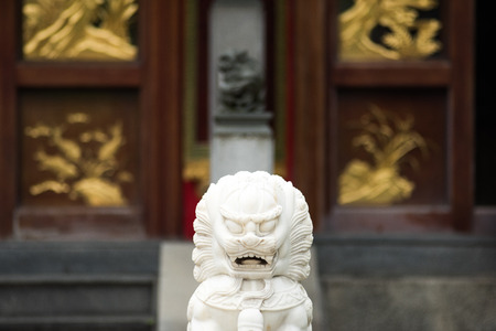 Ancient Temple architecture: white stone animal statue in front of entrance