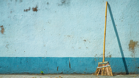 Broom and blue wall