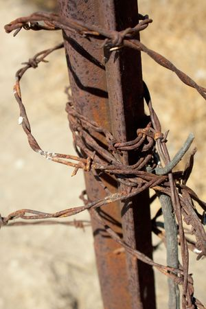 A vertical close-up shot of a knotted tangle of rusty barbed wire attached to an old post in southern California. Stock Photo - 7657923