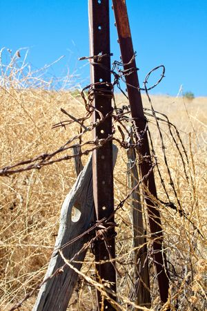 A vertical close-up shot of rusty barbed wire and rotting wooden fence posts in a dry summer field in southern California. photo