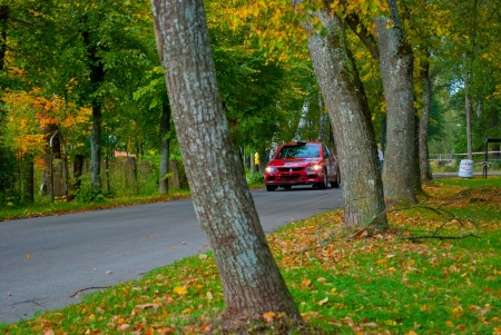Red racing car in autumn road