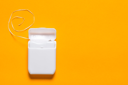 Dental floss on yellow background