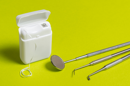 Dental floss and instruments on green background