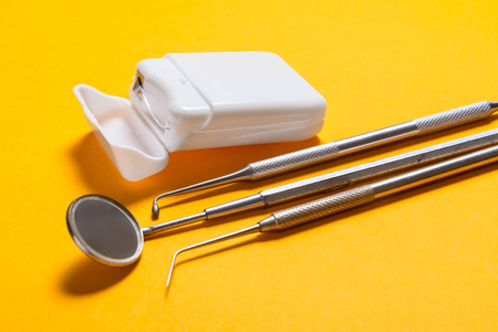 Dental floss and instruments on yellow background