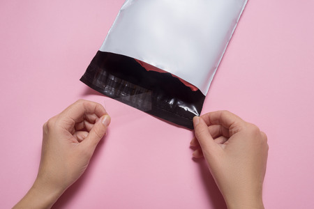 Woman closing white polythene envelope Stock Photo