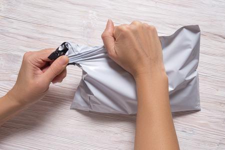women hands tear polythene envelope