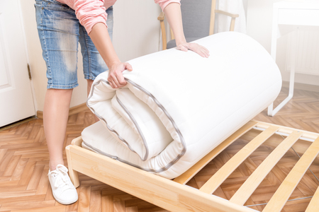 Woman unrolling new mattress