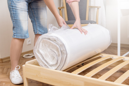 Woman unrolling new mattress