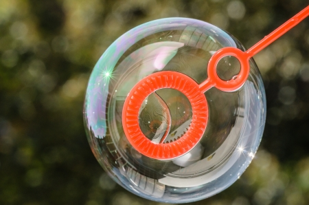 blowing bubbles: Close up of a soap bubble growing from the blower ring Stock Photo