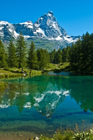 mountain meadow: the Matterhorn reflected in the clear waters of blue lake, Valtournenche - Aosta Valley Stock Photo