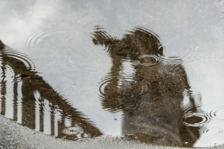 photographer reflected in a puddle on a rainy day