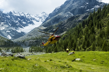alpine helicopter rescue and doctor on the meadow Stock Photo