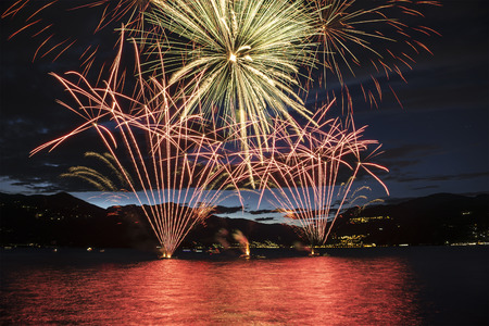 Lakefront Luino fireworks on the Maggiore lake in summer evening, Lombardy - Italy