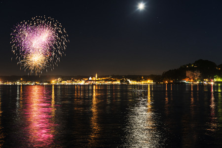 Fireworks on the lakefront of Arona in a summer party night - Piedmont