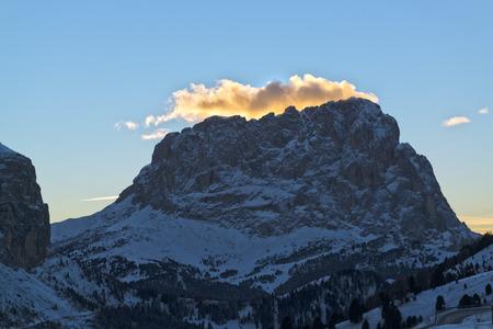 nubi illuminate dal sole al tramonto sul Sassolungo in inverno, Dolomiti
