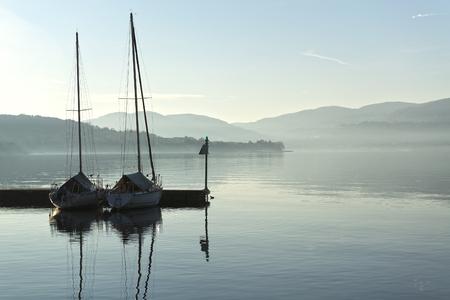 due barche nel porto di un lago calmo e le nebbie orizzonte invernale Archivio Fotografico
