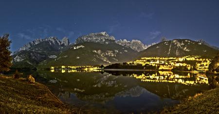 Paesaggio notturno del Lago di Molveno e Dolomiti di Brenta Gruppo in una tranquilla serata estiva con cielo stellato sullo sfondo, Trentino - Italia