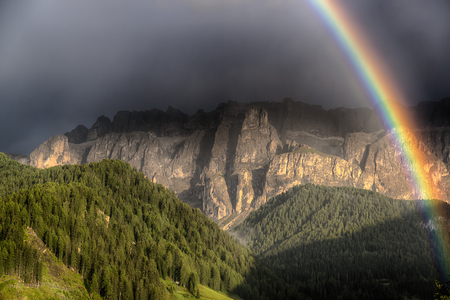 Rainbow after the thunderstorm over the hills and mountains of Selva di Val Gardena in a summer end of the day, Trentino-Alto Adige - Italy
