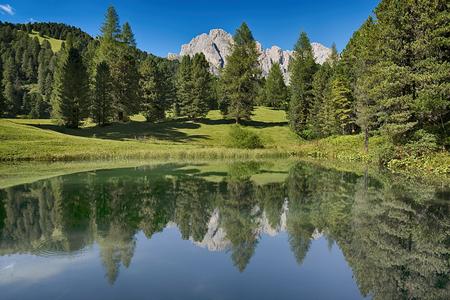 Lago nella foresta con le montagne sullo sfondo, la stagione estiva - Trentino-Alto Adige, Dolomiti