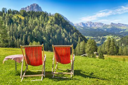 sedie a sdraio e tavolo sul prato con vista sulle montagne e sulla valle in estate Archivio Fotografico