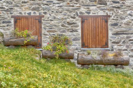 due finestre e tre vasi di fiori sul prato in pendenza Archivio Fotografico