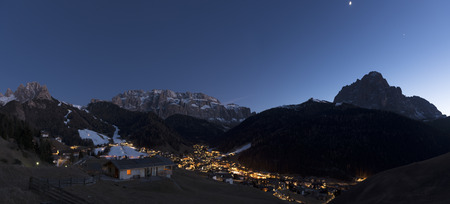 blue hour in Selva di Val Gardena with the moon above the Sassolungo Group profile