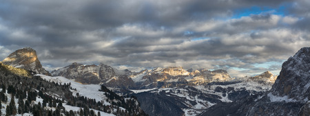 Sunset over mountains of Alta Badia in a winter end of the day with cloudy sky , Dolomites