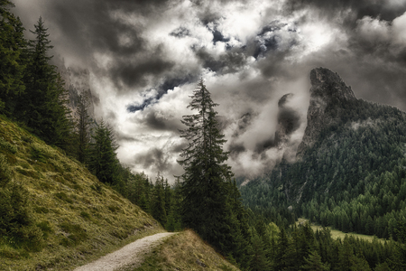 selva: path through the forest with the top of the mountains wrapped in threatening clouds, Vallunga near the little city of Selva di Val Gardena - Trentino-Alto Adige
