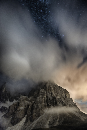 Cimon della Pala in the night with clouds and stars