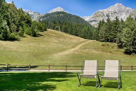 Two deck chairs on the meadow with panoramic mountain views in the background, Molveno