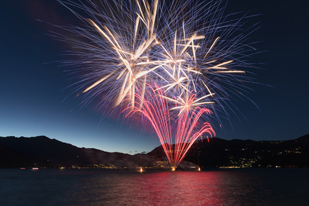 Fireworks on the lakefront of Luino over the Major Lake in a summer evening with blue sky and mountains in the background