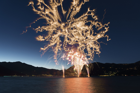 Fireworks on the lakefront of Luino over the Maggiore Lake in a summer evening with blue sky and mountains in the background Archivio Fotografico