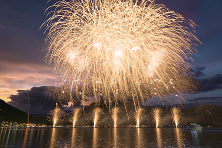 Fireworks on the Lugano Lake in a summer evening with cloudy sky at the sunset in the background Archivio Fotografico