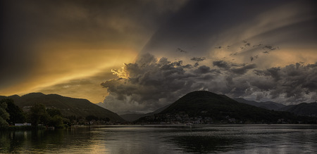 Sunset over the Lugano Lake in a end of the summer day with cloudy sky and ray of sunny light