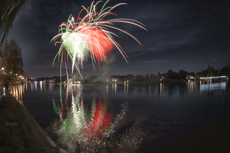 Fireworks on the river Ticino in a summer evening with landscape in the background