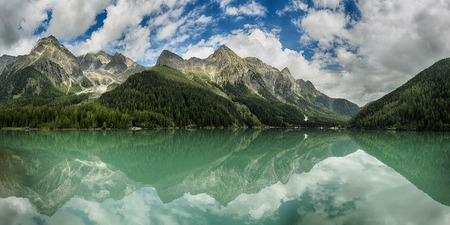 Lake of Anterselva surrounded by mountains with blue sky and clouds in the background on a summer day, Sud Tirol, Italy Stock Photo