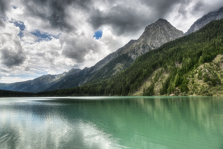 Lake of Anterselva surrounded by mountains with blue sky and dark clouds in the background on a summer day, Sud Tirol, Italy Stock Photo