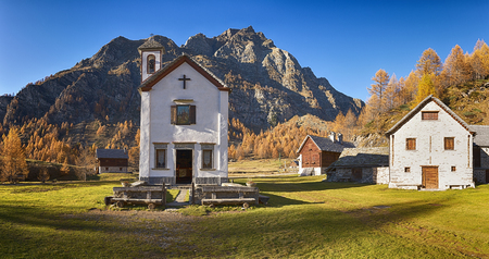 renovated: Small church in ancient village at sunset in autumn season with long shadow on the green grass Stock Photo