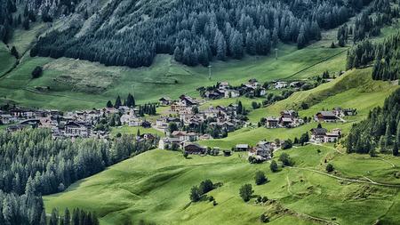 Little village of Colfosco on the hills with green meadow in summer season, Alta Badia - Trentino-Alto Adige, Italy Editorial