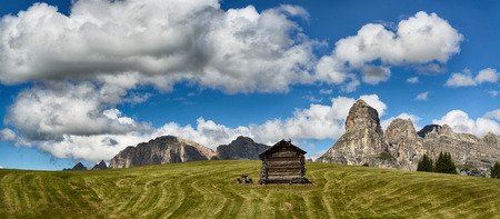 Landscape of mountains of Alta Badia in the Dolomites in summer season with green meadow in foreground, Italy Editorial