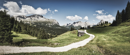 Vintage landscape of  mountains of Alta Badia in summer season with path in foreground and sky and clouds in background, Dolomites - Italy