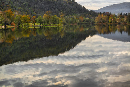 Lake of Ghirla and woods with autumn colors in background in a gray afternoon of November