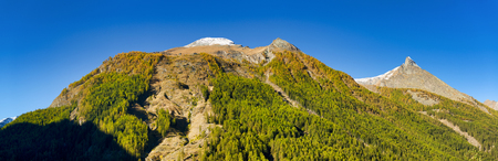 the summit of mountains with snow of Aosta Valley in a clear day and forest with first colors of autumn, Cogne - Italy Standard-Bild