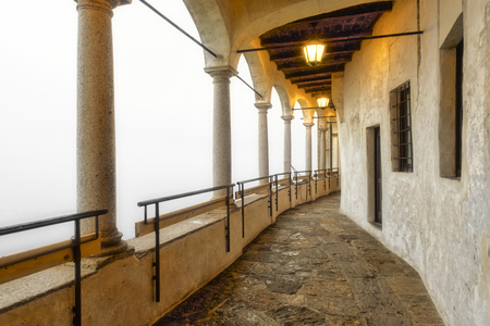 ancient portico with stone columns, warm light lamps and wooden ceiling in a foggy day