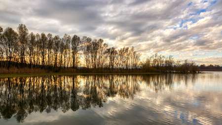 clouds reflected on Varese lake at sunset with trees, autumn panorama