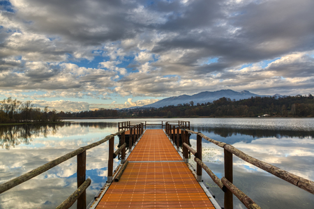 pier on the lake of Varese with cloudy sky at the autumn sunset