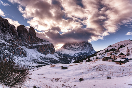 Winter landscape from Gardena Pass in the Dolomites at the sunset with clouds over the top, Italian mountains - Trentino Alto-Adige, italy
